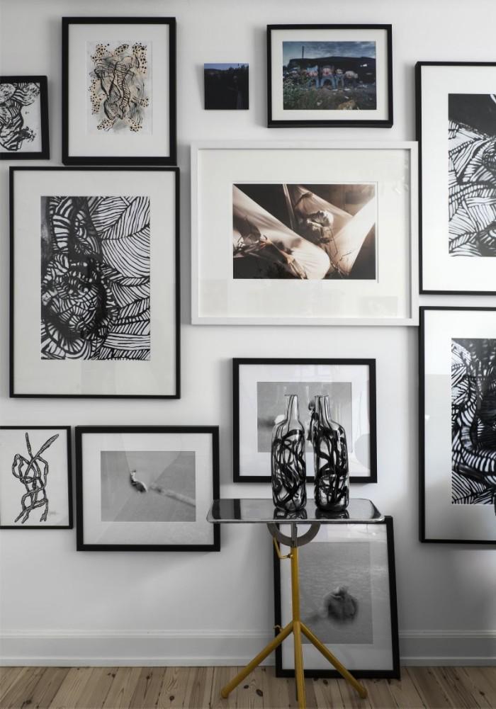 """Tavelvägg à la Bergström med egna verk blandat med samarbeten med fotografen Thomas Klementsson samt fotografier av Jenny Källman och Jouko Lehtola. """"Jag tycker att man ska köpa konst man älskar, inte sådant som är dyrt"""". Glasflaskor Firande en serie med skål och vas som kom 2015, Ikea."""