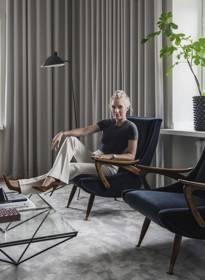 Hanna sitter i sina auktionsfynd, två fåtöljer som kläddes om i sammet. Krukor Hannas egen design, kan köpas via hannasroom.com. Golvlampa, Serge Mouille.