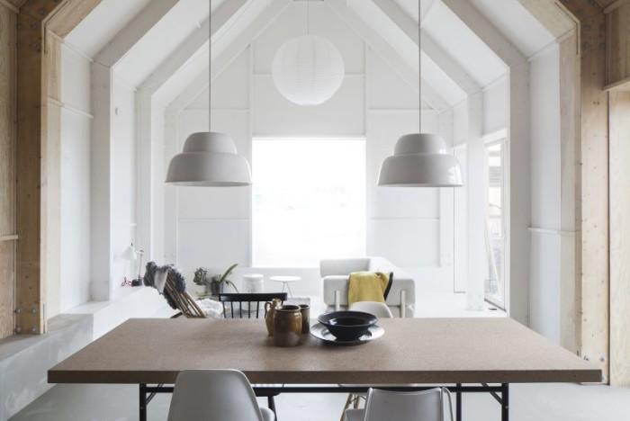 I det vitmålade vardagsrummet studsar södersolen vidare in i matsalen och köket. Över matbordet hänger pendelarmaturen Levels av Form us with love.