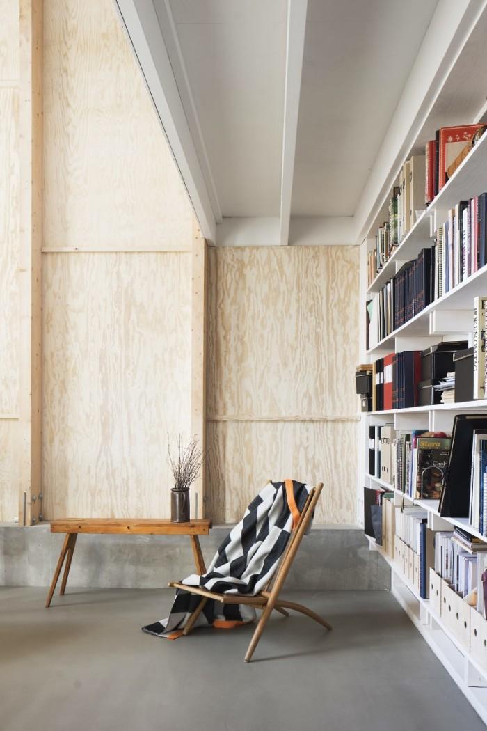 En bibliotekarie kräva bokhyllor. I ateljén sträcker sig hyllorna hela vägen från golv upp till taknock, närmare sju meter i höjdled. Ett utkragande mezzaninplan bryter av.