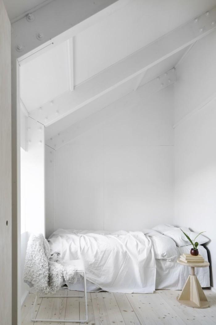 Ett av övervåningens två sovrum som nås via mezzaninplanet. Mikael Lings stapelbara trådstol i metall och trä ackompanjeras av ett nattduksbord från Hem.