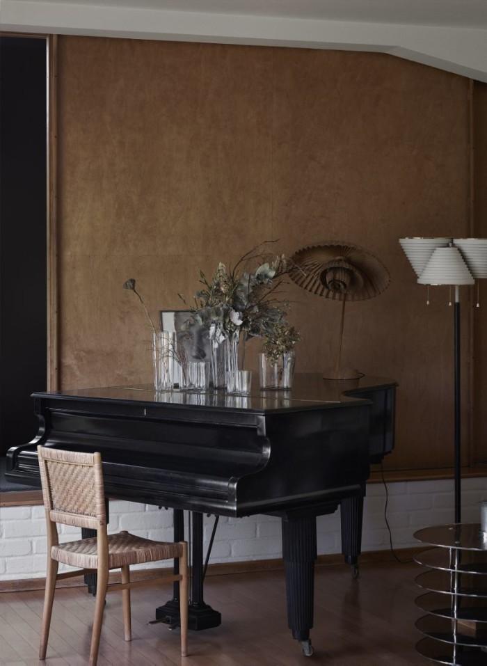 Vardagsrummet med vasen Savoy i olika storlekar på flygeln, alla Iittala. Bredvid pianot golvlampa A809, Artek. Plywooddörren är skjutbar och leder till Aaltos arbetsrum. På pianot ett porträtt av Aino och en lampa av Poul Henningsen. Pianostol, Aalto. Bordet är en prototyp från 1929.