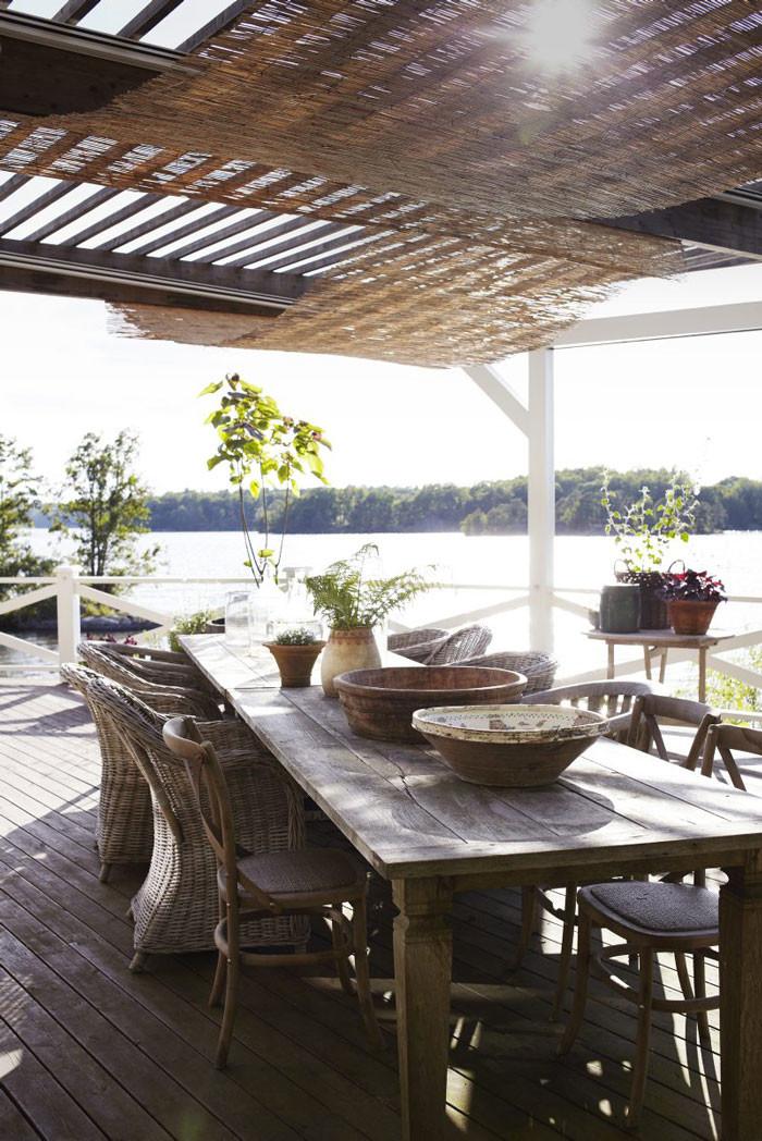 På den stora terrassen som ligger i söderläge har Johan och Victoria ställt två rejäla bord för alla gästabud. I taket hänger vassmattor som skuggar mot solen. I ekfaten i bakgrunden växer fliksumak och tulpanträd.