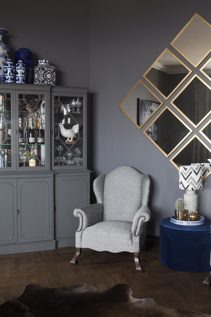 Det välfyllda barskåpet är målat i samma blågråa färg som väggen. Spegelmosaiken förlänger rummet ytterligare. All ekparkett i lägenheten är nylagd och behandlad med pigmenterad hårdvaxolja från Osmo. Den befintliga parketten var i för dåligt skick för att behålla. I taket hänger tre lyktor i glas och mässing från Spanien.