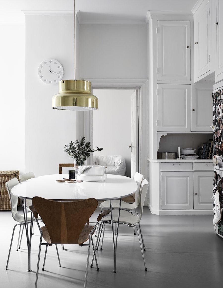 Bild på Anna Teurnells kök, taklampa i mässing och vitt matbord.