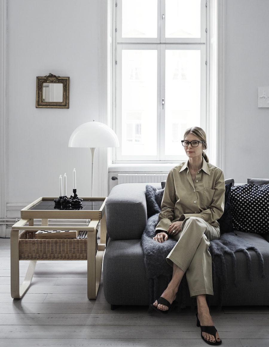 Anna Teurnell sitter i sin soffa i kläder från Arket.