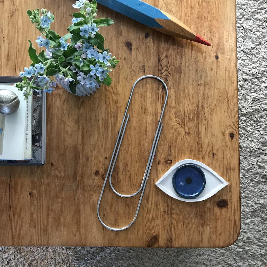 Bild på uppförstorat gem, öga och penna hemma hos Auktionstipsets Lisa Milberg.