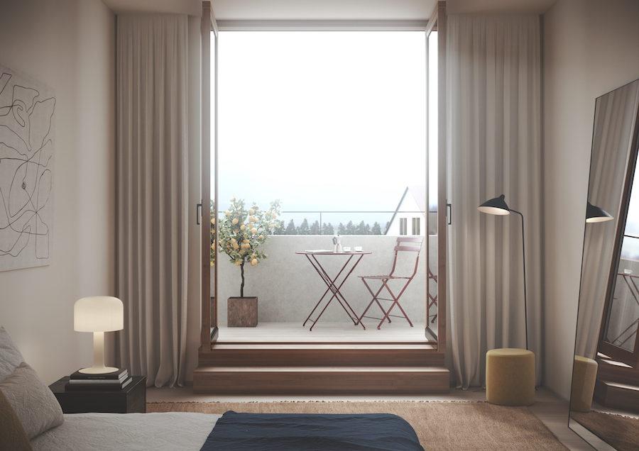 Ett av sovrummen i med balkong och stora glasdörrar.